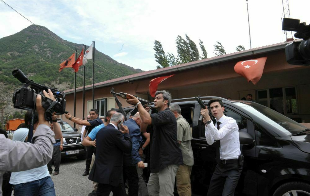 Bodyguards of Kemal Kilicdaroglu, leader of the main opposition Republican People's Party, direct their guns toward a mountain as he gets into a car after an attack in Savsat, Artvin, Turkey, Thursday, Aug. 25, 2016. Kurdish rebels opened fire on Thursday at security forces protecting a convoy of vehicles carrying Turkey's main opposition party leader in the northeast of the country, wounding three soldiers, Turkey's interior minister said. Kilicdaroglu told the state-run Anadolu Agency that he was safe and had been taken to a government building in Artvin province.(AP Photo)