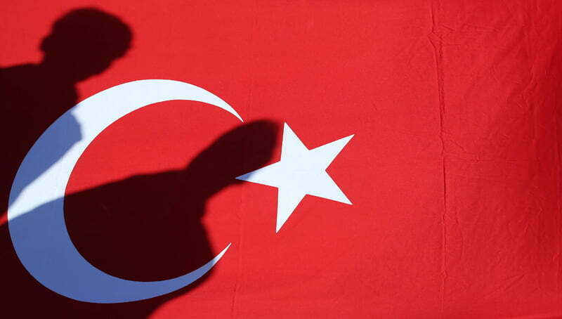 epa05373431 Turkish fans cast a shadow on their national flag before the UEFA EURO 2016 group D preliminary round match between Spain and Turkey at Stade de Nice in Nice, France, 17 June 2016. (RESTRICTIONS APPLY: For editorial news reporting purposes only. Not used for commercial or marketing purposes without prior written approval of UEFA. Images must appear as still images and must not emulate match action video footage. Photographs published in online publications (whether via the Internet or otherwise) shall have an interval of at least 20 seconds between the posting.)  EPA/OLIVER WEIKEN   EDITORIAL USE ONLY