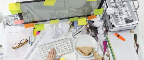 Office wotker at messy office desk eating a sandwich
