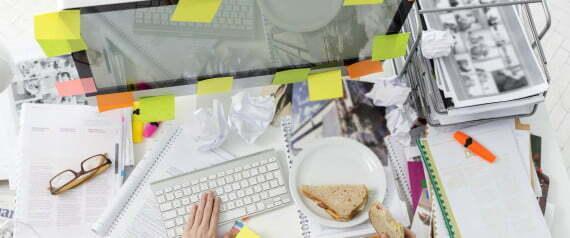 Office wotker at messy office desk eating a sandwich